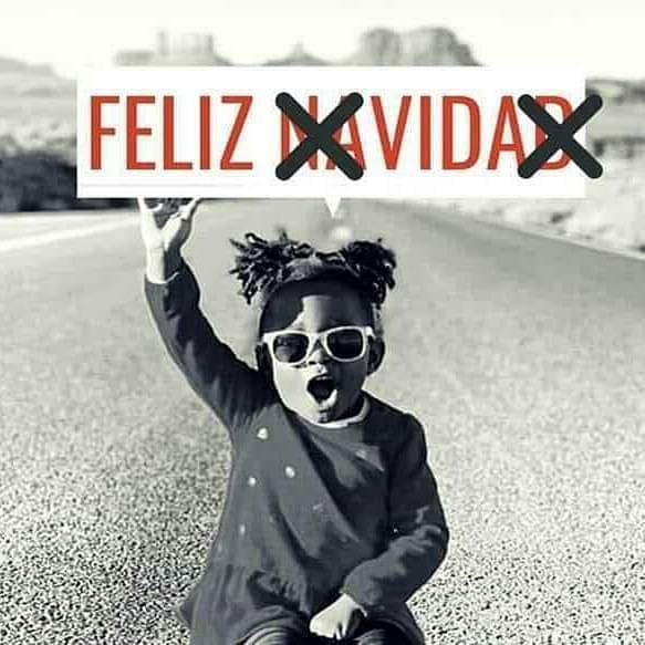 una niña antisistema, diciendo feliz navidad, tachando el cartel, poniendo feliz vida